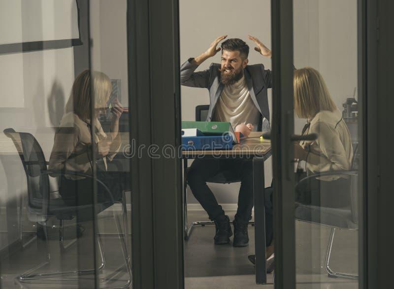 充满愤怒的有胡子的人呼喊对妇女在办公室 有胡子的人和金融家谈论公司预算和金钱危机 免版税库存图片