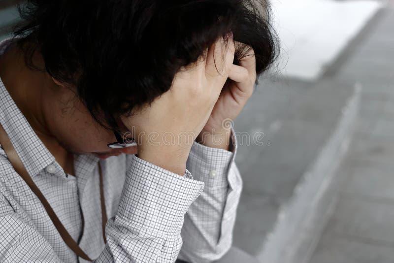充满手和感觉的沮丧的被注重的年轻亚洲商人覆盖物前额失望在外部办公室 免版税库存照片