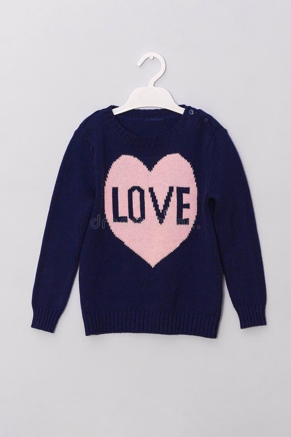 充满样式桃红色心脏和题字爱的女性蓝色毛衣在灰色背景的挂衣架 妇女时尚神色衣裳 免版税库存照片