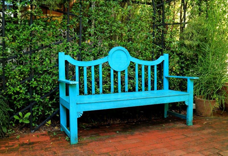 充满活力的土耳其玉色上色了在赤土陶器砖路的长木凳 免版税库存照片