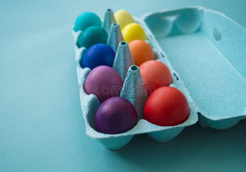 充满活力的手在被观看的纸板蛋盒的被洗染的五颜六色的复活节彩蛋 库存图片