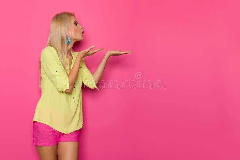 充满活力的衣裳的美丽的白肤金发的妇女送飞吻 库存图片