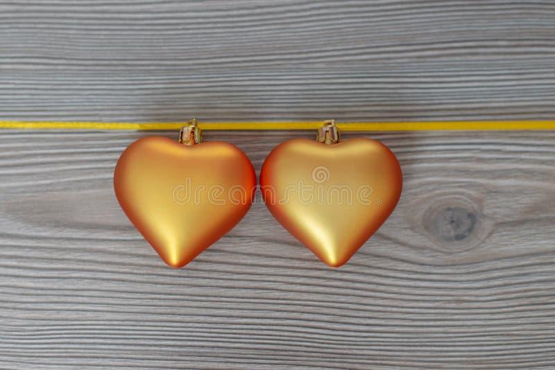 充满爱的圣诞节静物画对亲人,在一条金丝带的两金黄心脏在木背景 华伦泰` s日礼品 免版税库存照片