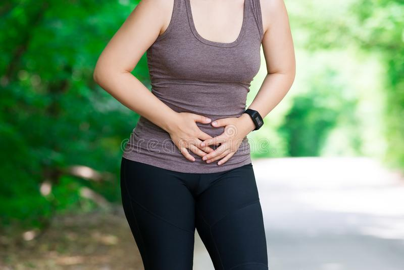 充满胃肠痛苦,伤害的妇女,当跑,创伤在锻炼期间时 图库摄影