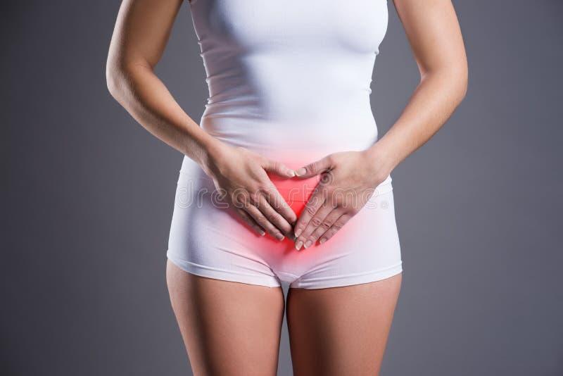 充满胃肠痛苦,在灰色背景的stomachache的妇女 库存图片
