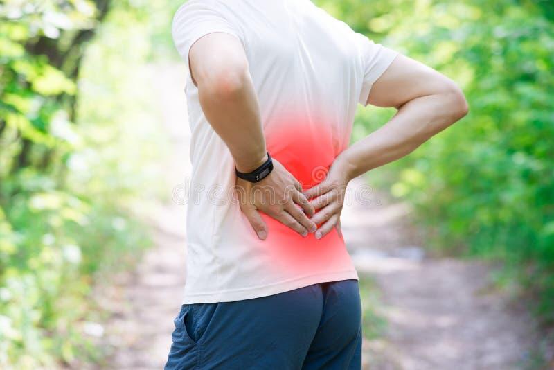 充满背部疼痛,伤害的人,当跑,创伤在锻炼期间时 免版税图库摄影