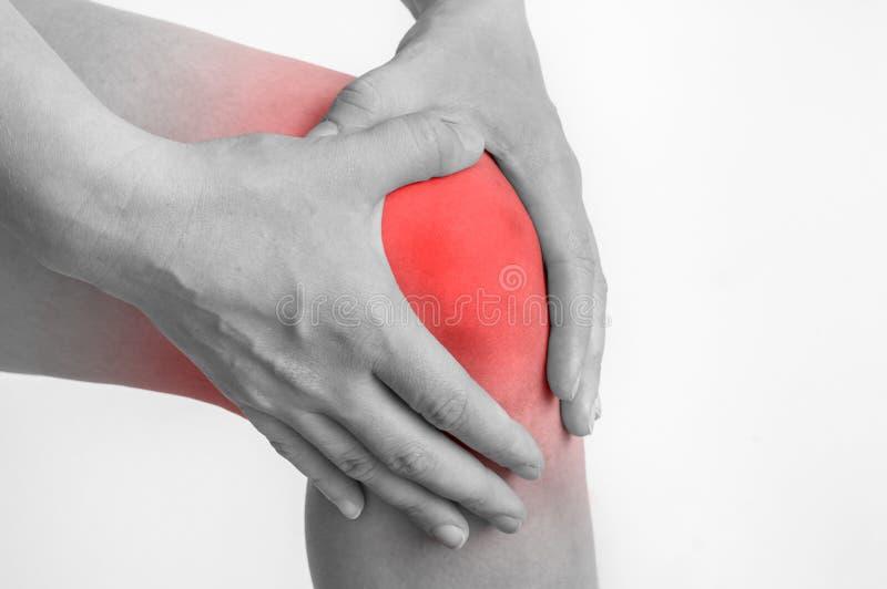 充满膝盖痛苦的妇女握她酸疼的腿 库存图片