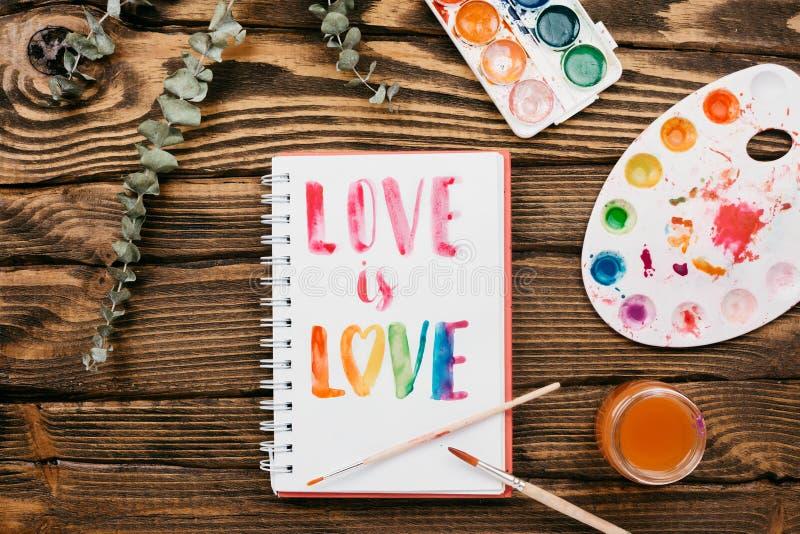 充满handlettering的题字`爱的写生簿是在木桌上的爱` 免版税图库摄影