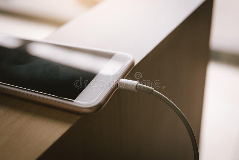 充电与力量银行的智能手机在木桌 免版税库存照片