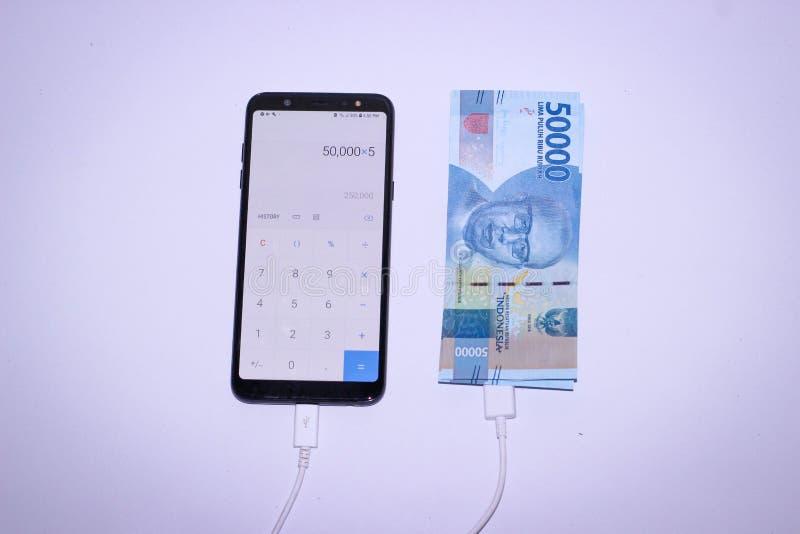 充电与印度尼西亚金钱的Handphone 图库摄影