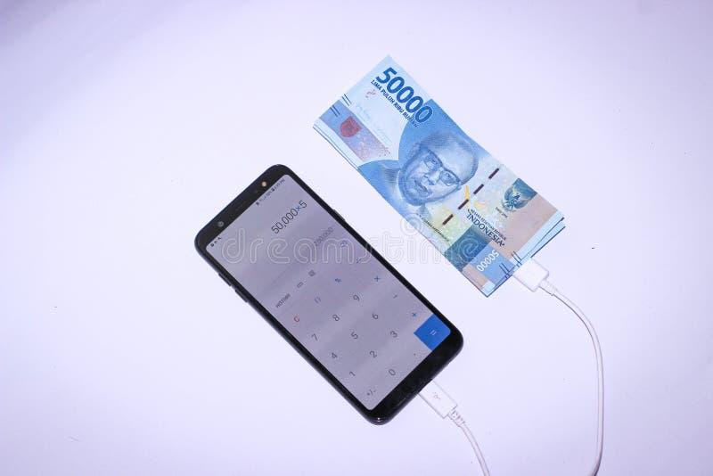 充电与印度尼西亚金钱的Handphone 库存照片