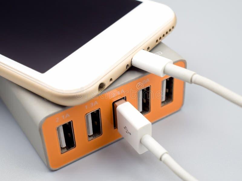 充电与multiport USB力量适配器的智能手机 免版税库存图片