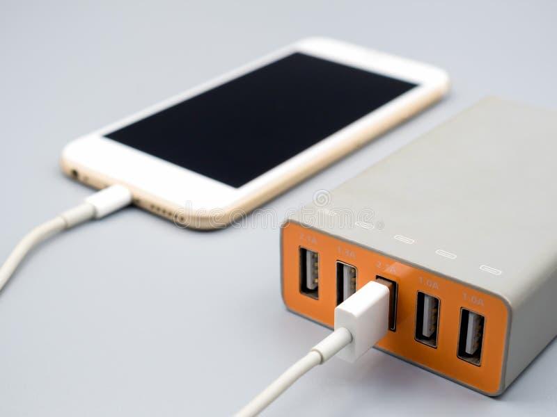 充电与multiport USB力量适配器的智能手机 免版税库存照片