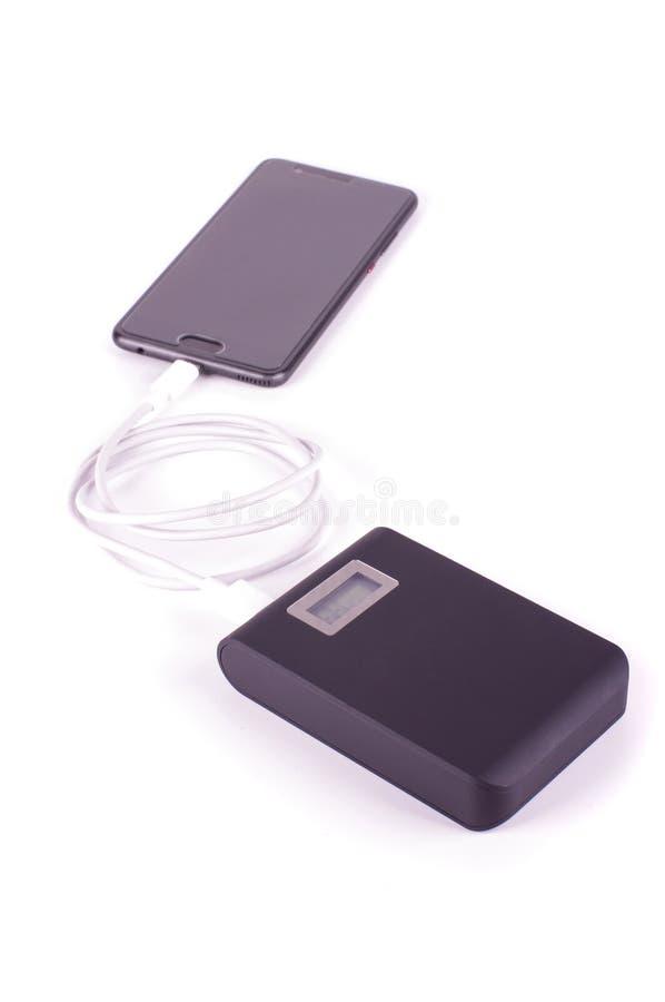 充电从力量银行的智能手机被隔绝在白色背景 图库摄影