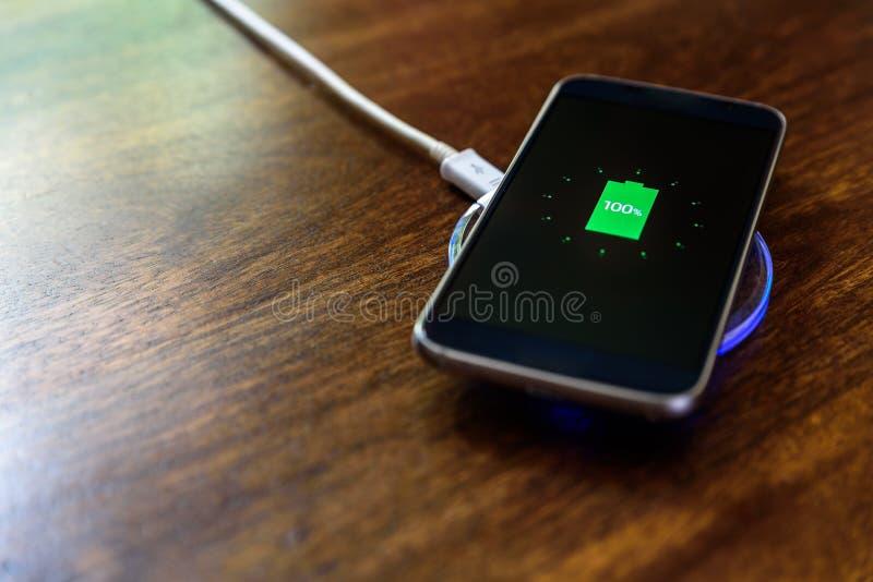 充电在一个充电的垫的智能手机 充电的无线 免版税库存图片