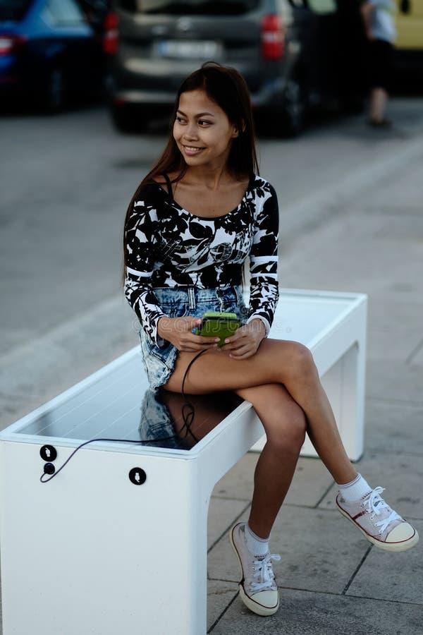 充电她的电话的美丽的妇女在自由多用途太阳电池板充电器合并了对公民的坐的长凳 现代t 库存照片