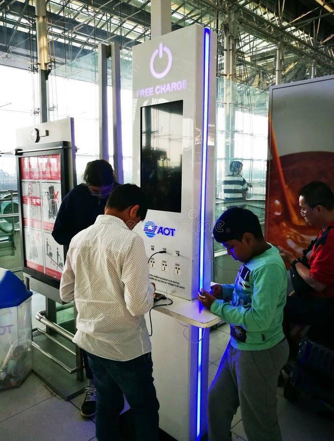 充电手机电池的旅客在免费服务充电站区域在素万那普国际机场在曼谷, 库存照片