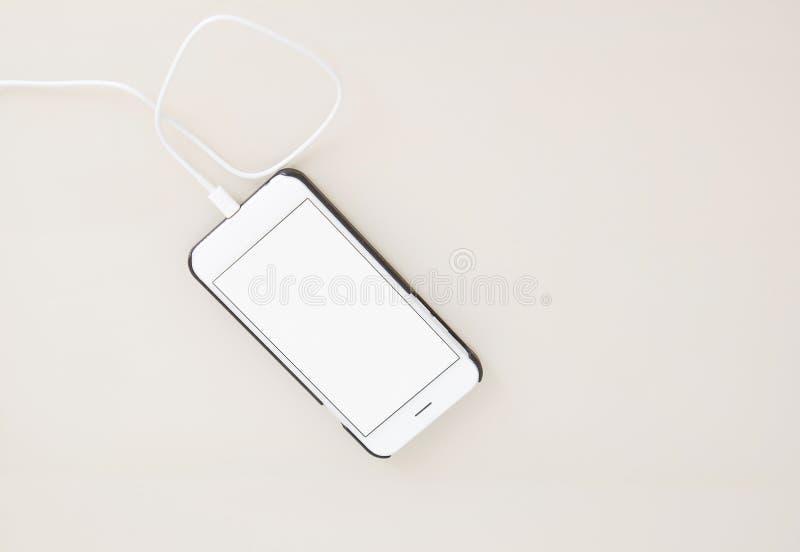 充电的智能手机,在木桌,黑屏手机上的手机 选择聚焦 复制空间,删去,嘲笑,顶视图 免版税库存图片