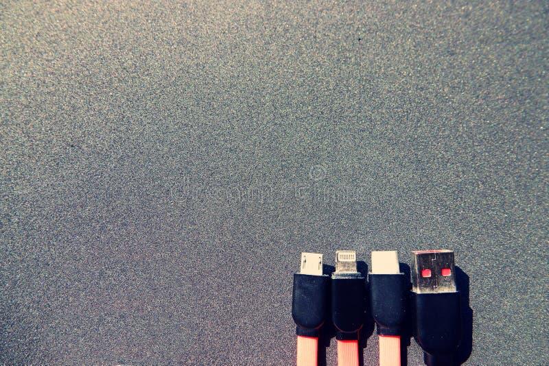 充电的缆绳的四种类型在黑背景前面的与拷贝空间 免版税图库摄影