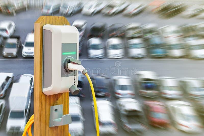 充电Ev驻地的电动车与Ev汽车的电缆供应插座在许多汽车迷离背景 图库摄影
