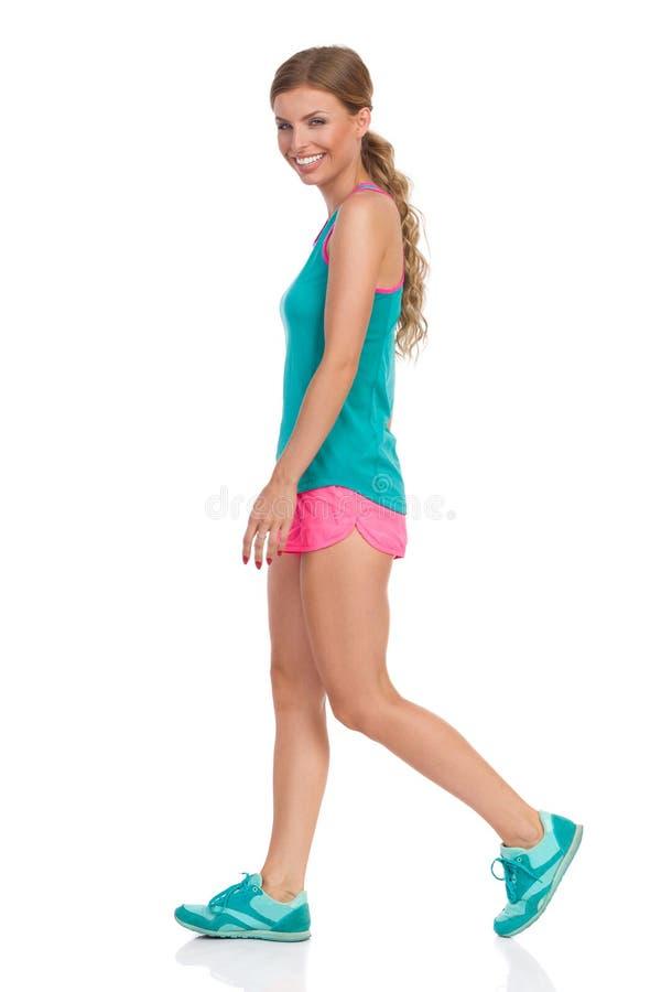 充满活力体育衣裳走的微笑的妇女 免版税库存照片