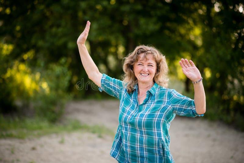 充满喜悦的白种人成熟妇女跳舞 免版税图库摄影