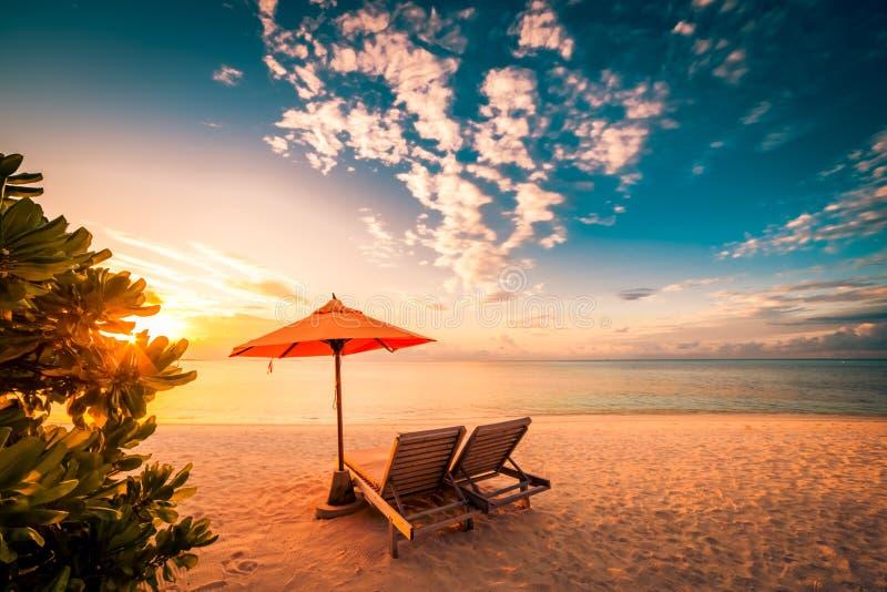 充满太阳床和松弛心情的美好的海滩日落 免版税库存照片