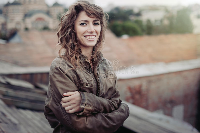 充满好心情的年轻可爱的妇女享受美好的城市风景的,当站立在大厦,迷人的微笑的臀部时屋顶  免版税库存照片