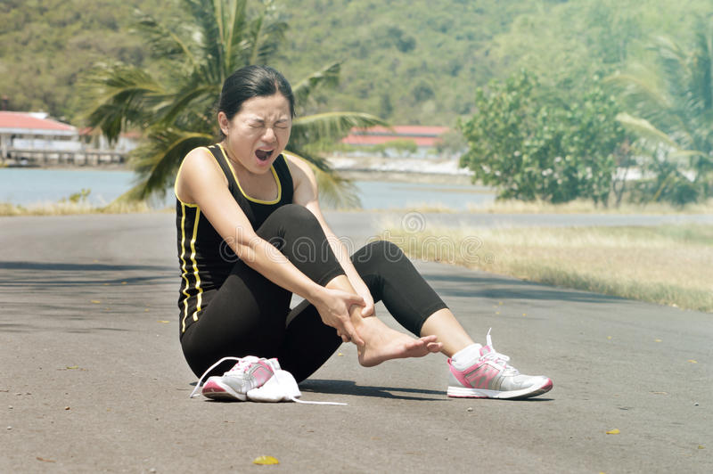 充满痛苦的妇女在脚腕,当跑步时 库存图片