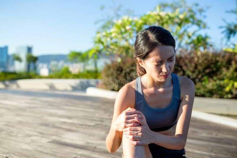 充满痛苦的妇女在膝盖关节体育锻炼 免版税库存照片