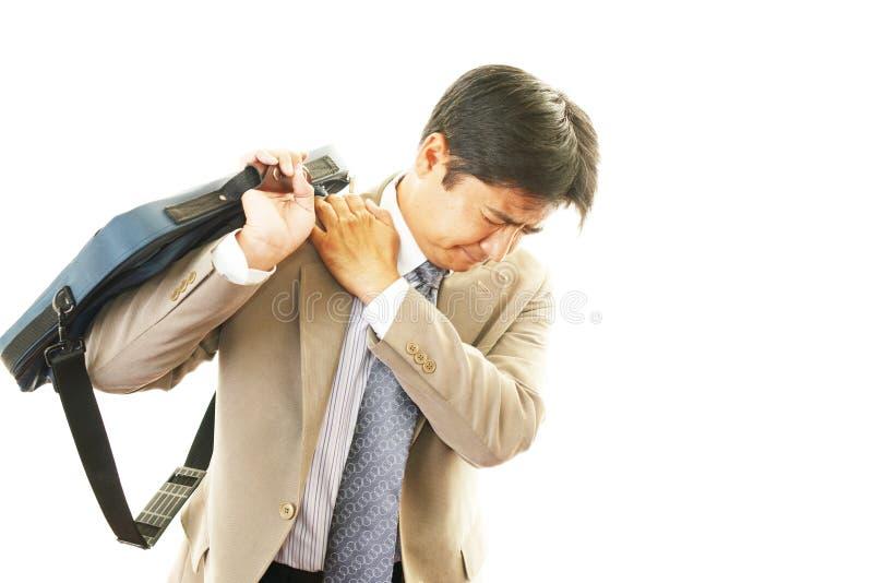 充满肩膀痛苦的商人。 免版税图库摄影