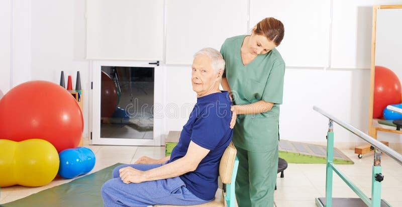 充满背部疼痛的老人在物理疗法 免版税库存照片