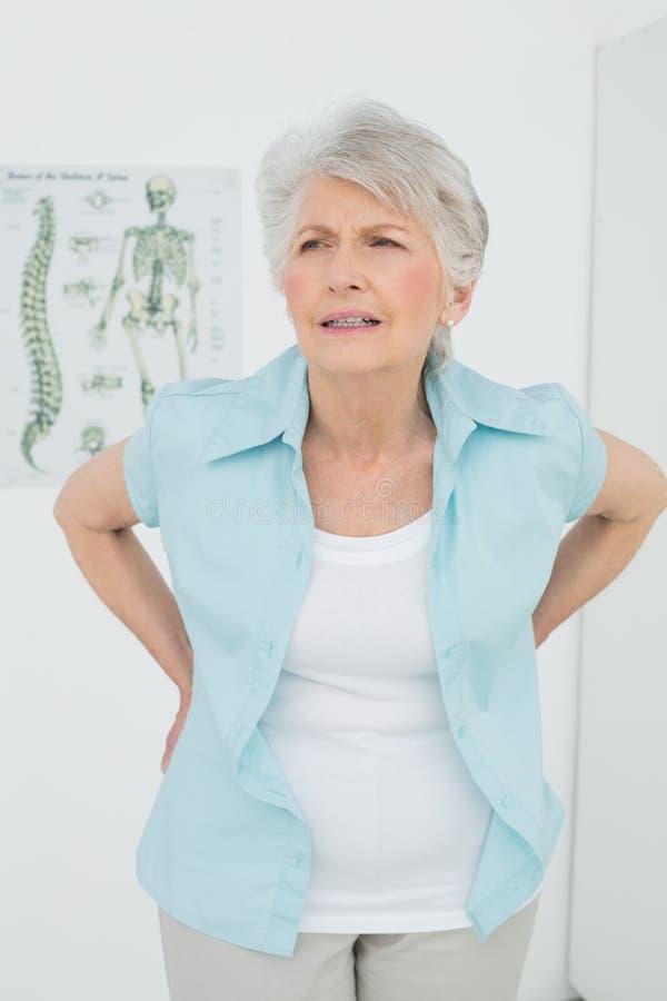 充满背部疼痛的资深妇女在医疗办公室 图库摄影