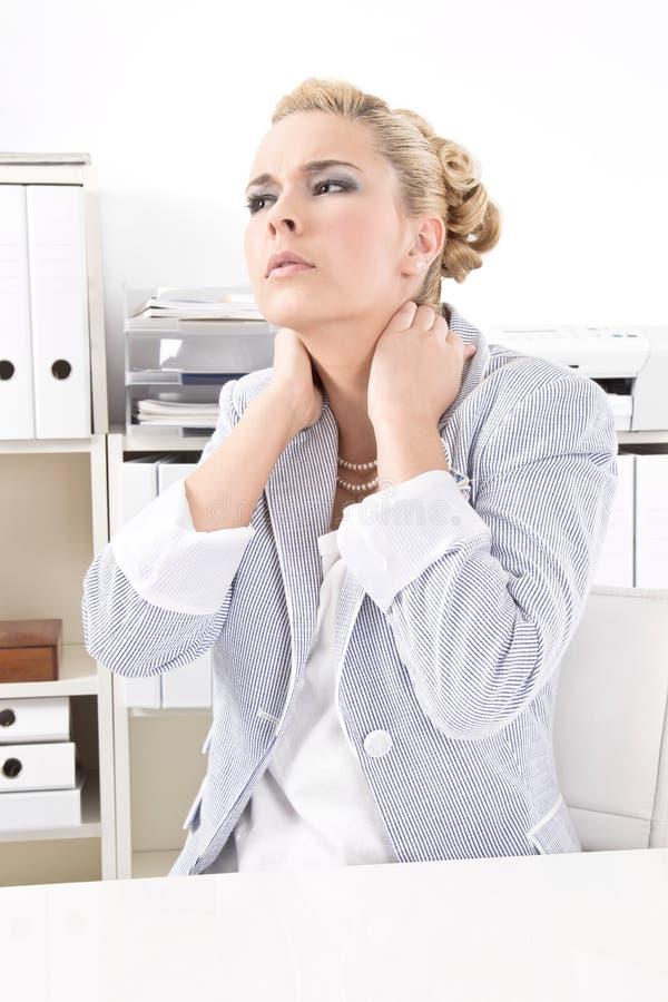 充满脖子痛的女商人 免版税库存照片