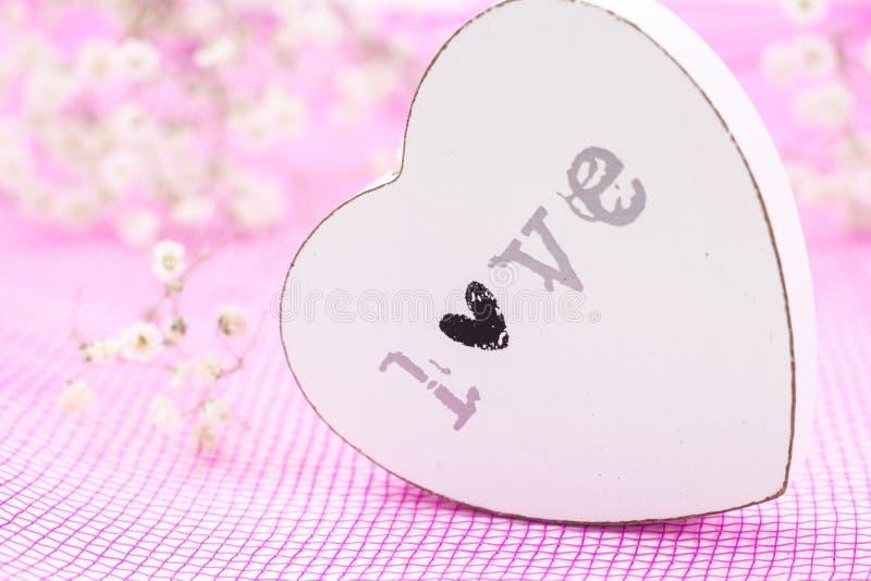 充满词爱的白色木心脏特写镜头,在桃红色网眼织物和白花 库存图片