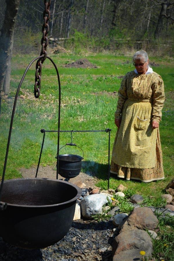 先驱妇女烹调 图库摄影