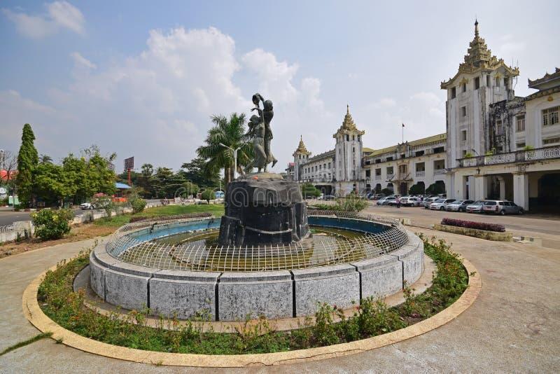 仰光中央火车站前面门面与用雕象装饰的圆的池塘喷泉的 免版税库存图片