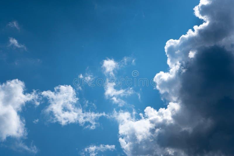 光亮云彩设置了反对深蓝天空在阳光下 美妙的蓝色发光的云彩 免版税库存照片