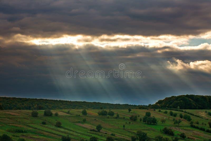 光从太阳的通过在绿色领域的灰色云彩 免版税图库摄影