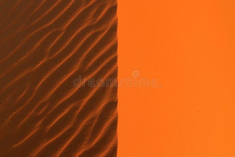 光和阴影对称地解剖橙色沙丘 免版税库存照片