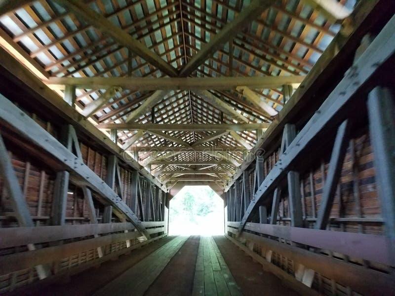 光在木被遮盖的桥结束时 库存图片