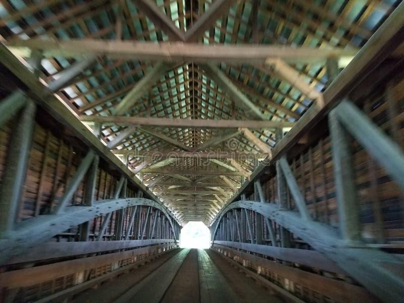 光在木被遮盖的桥结束时 图库摄影