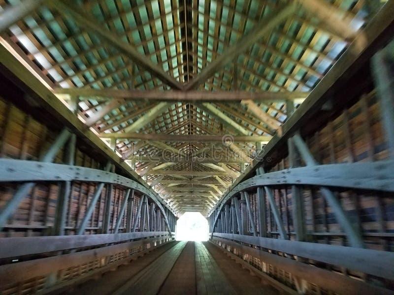 光在木被遮盖的桥结束时 库存照片
