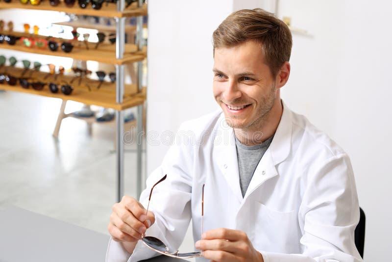 光学沙龙的微笑的眼镜师 免版税图库摄影
