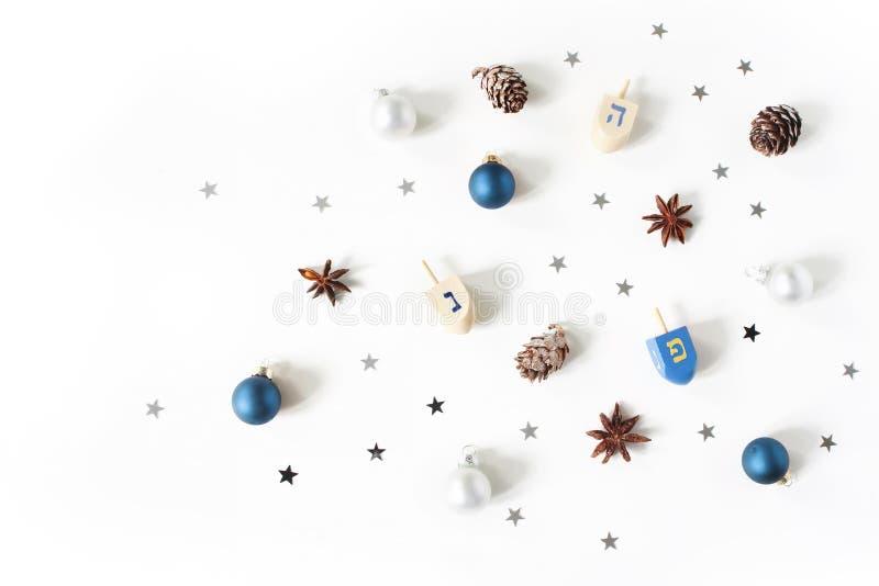 光明节称呼了储蓄构成 装饰模式 木dreidel玩具、落叶松属锥体、茴香和银色五彩纸屑星 免版税库存图片