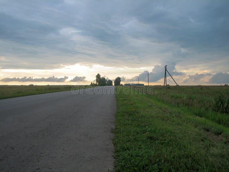 光滑的平直的柏油路在乡下在与云彩的天空下在日落 免版税库存图片