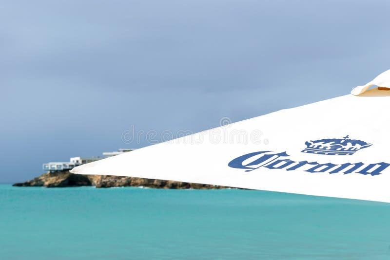 光环品牌/被烙记的沙滩伞有绿松石海洋的和风雨如磐的云彩在背景中 免版税库存图片