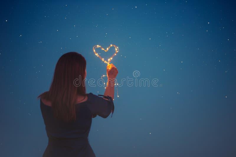 光的心脏在妇女` s手上 免版税图库摄影