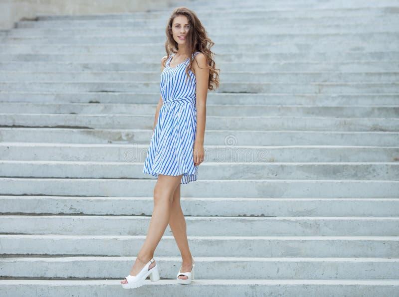 光的年轻愉快的嬉戏的妇女镶边了摆在具体楼梯的白色蓝色礼服室外 库存照片