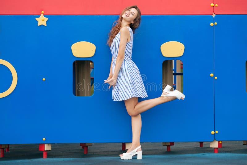 光的年轻深色的妇女镶边了白色蓝色礼服获得乐趣在室外的操场 库存照片